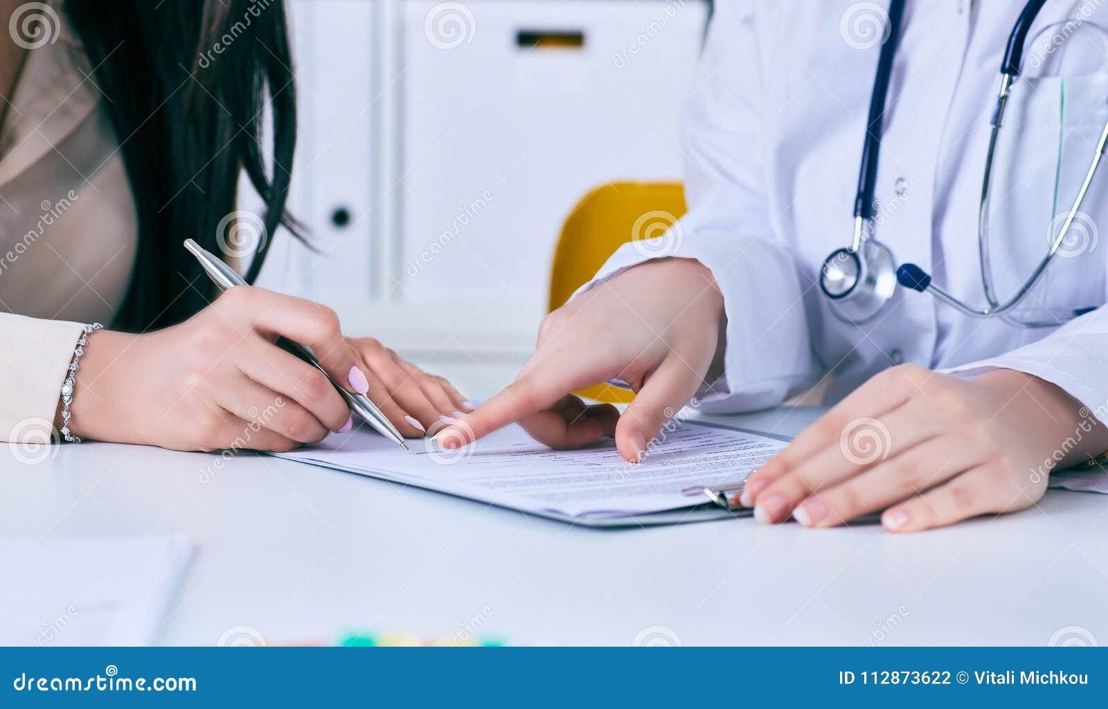 Paziente che firma contratto medico Medico femminile spiega come riempire la forma medica