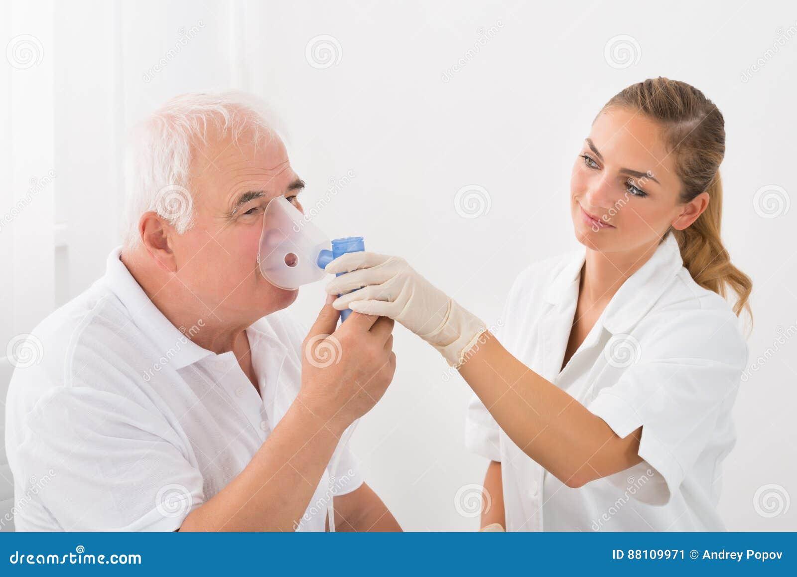 Paziente che inala attraverso la maschera di ossigeno