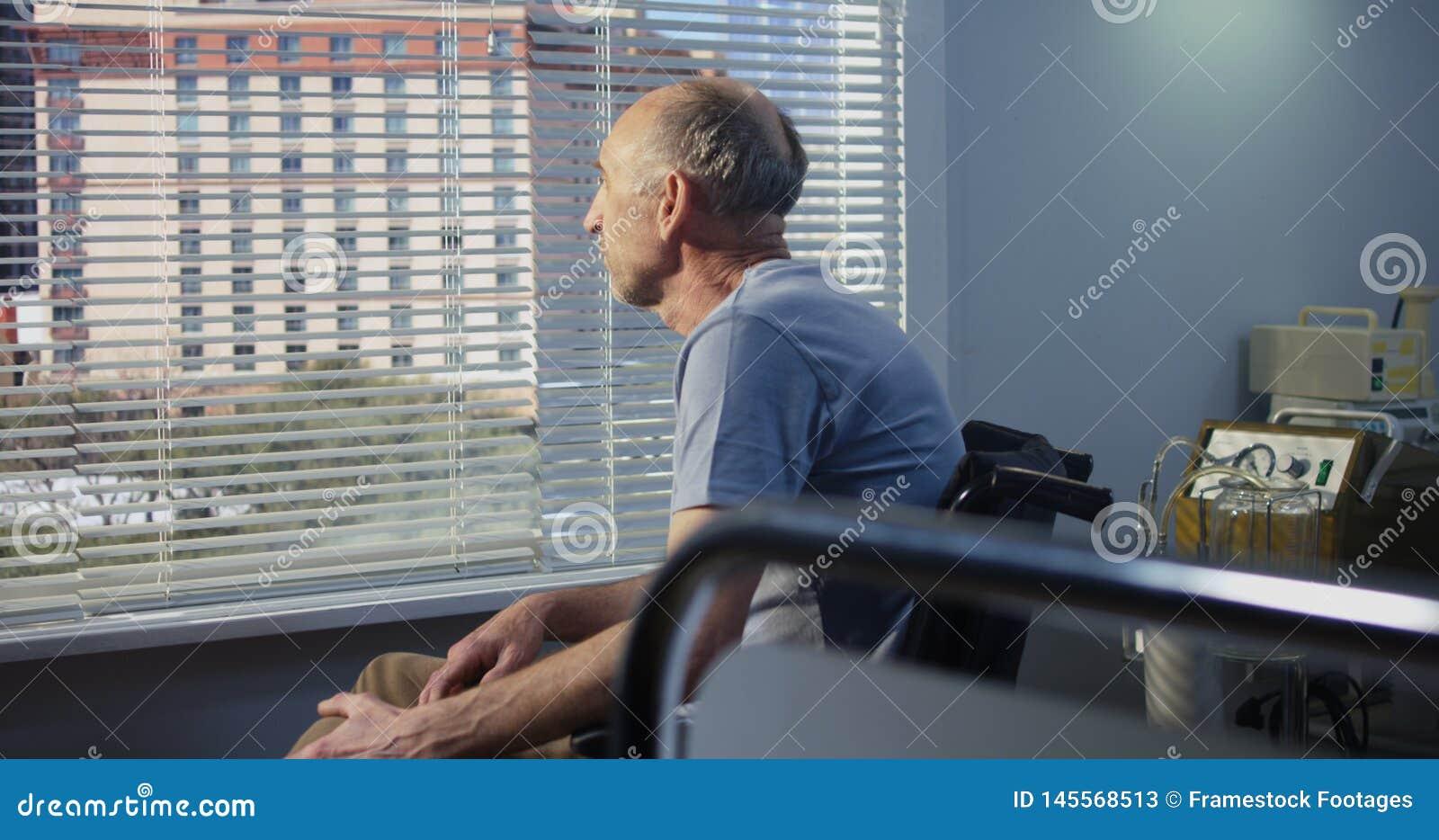 Paziente maschio anziano in ospedale vicino alla finestra
