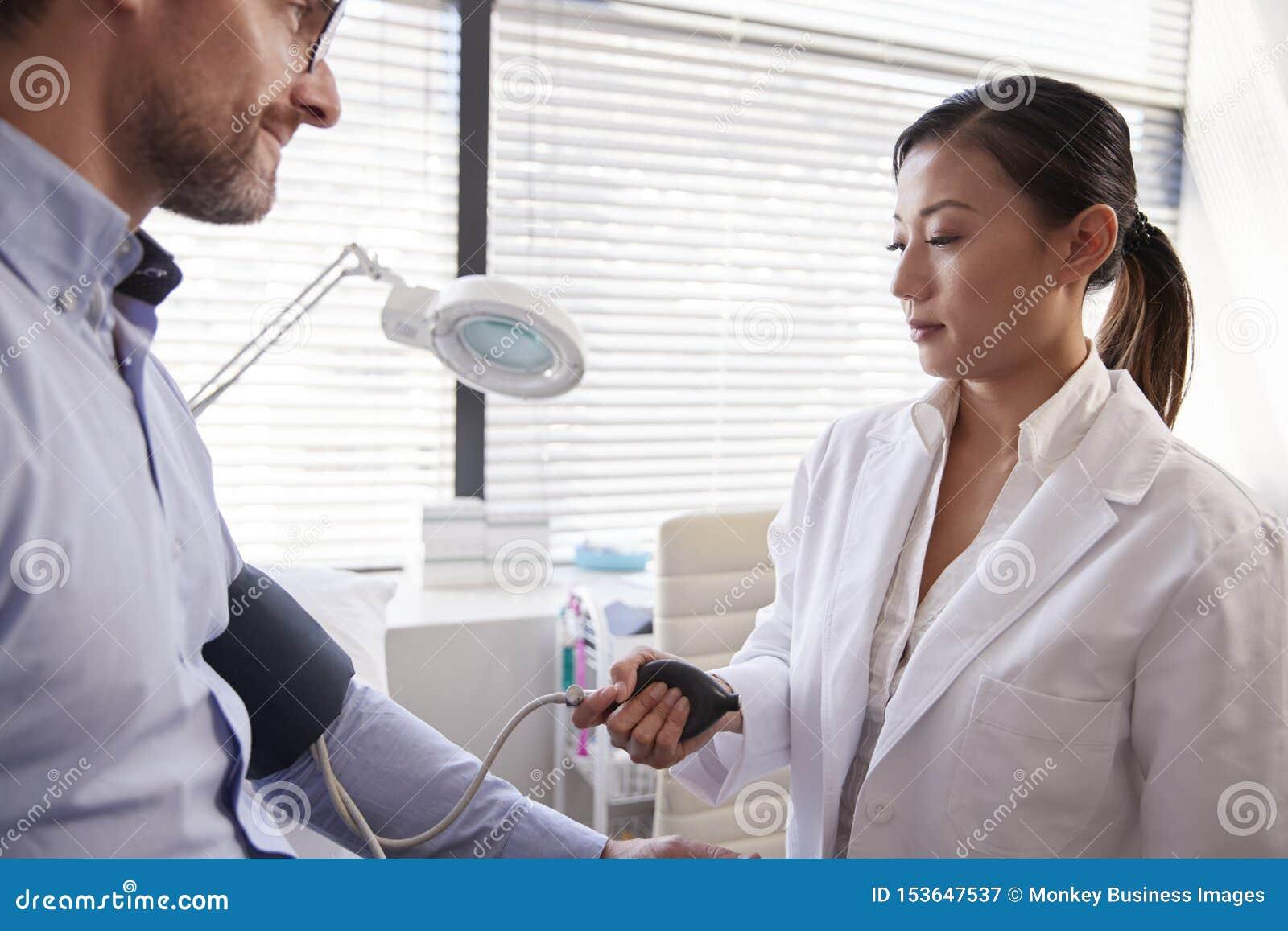 Paziente maschio che fa prendere pressione sanguigna dal dottore femminile In Office