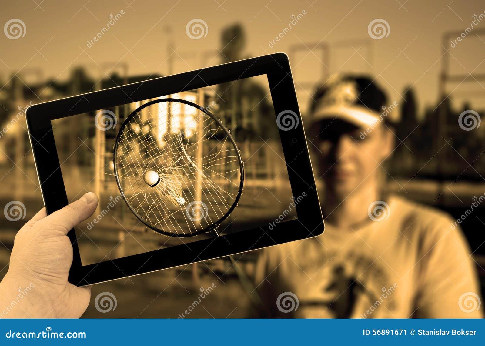 PC della compressa della foto a disposizione con la racchetta di volano lacerata di tennis con il volano attaccato dentro durante