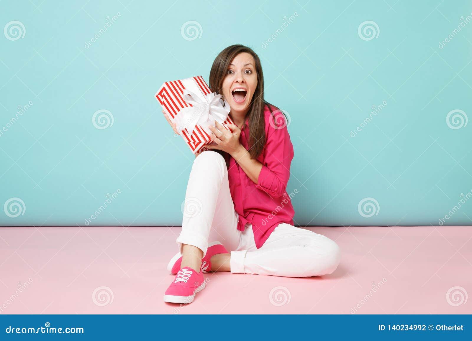 Pełna długość portreta kobieta siedzi na podłogowym chwyt teraźniejszości pudełku odizolowywającym na jaskrawych menchiach w róża