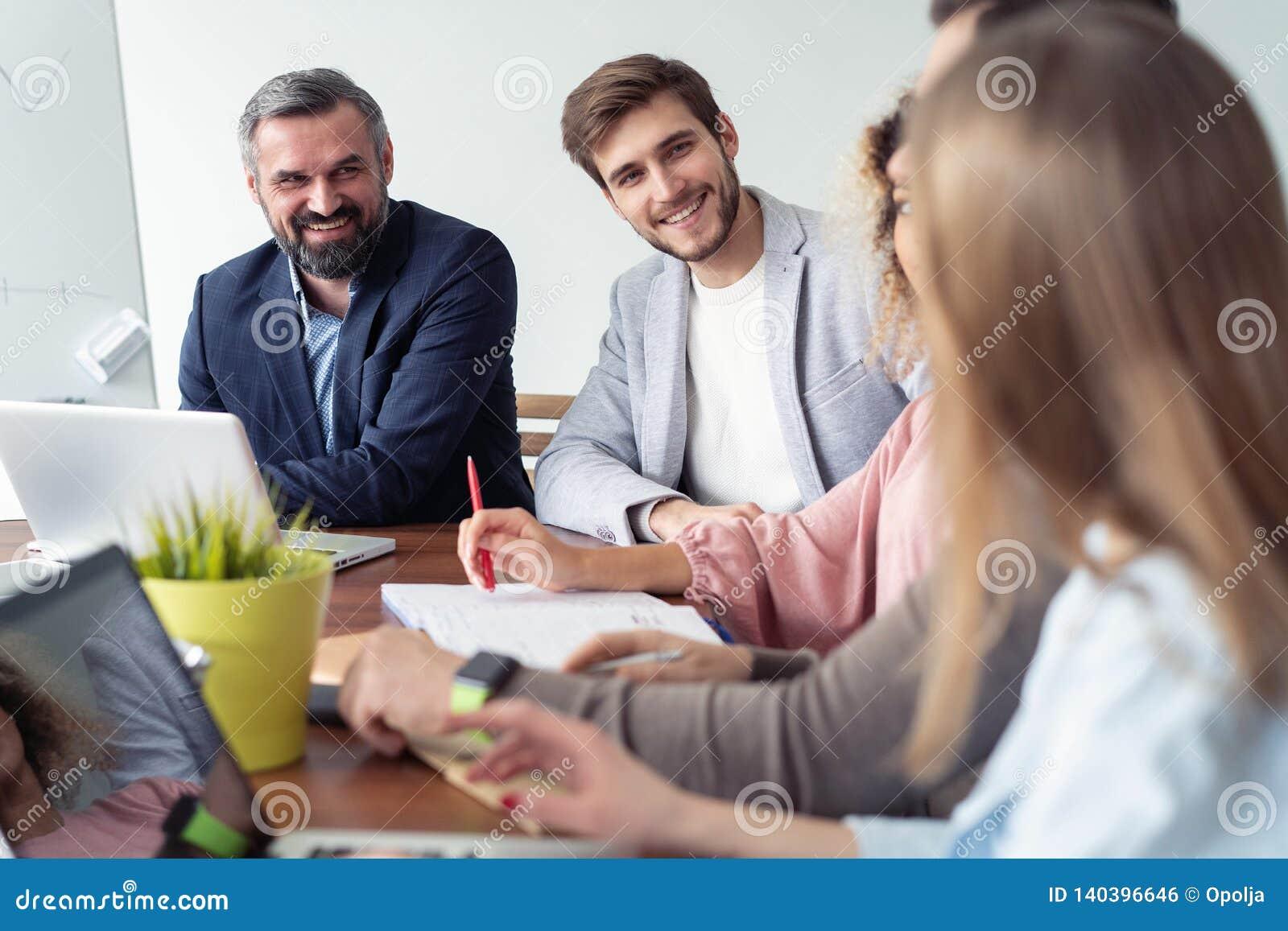 Pełna koncentracja przy pracą Grupa młodzi ludzie biznesu pracuje i komunikuje podczas gdy siedzący przy biurowym biurkiem