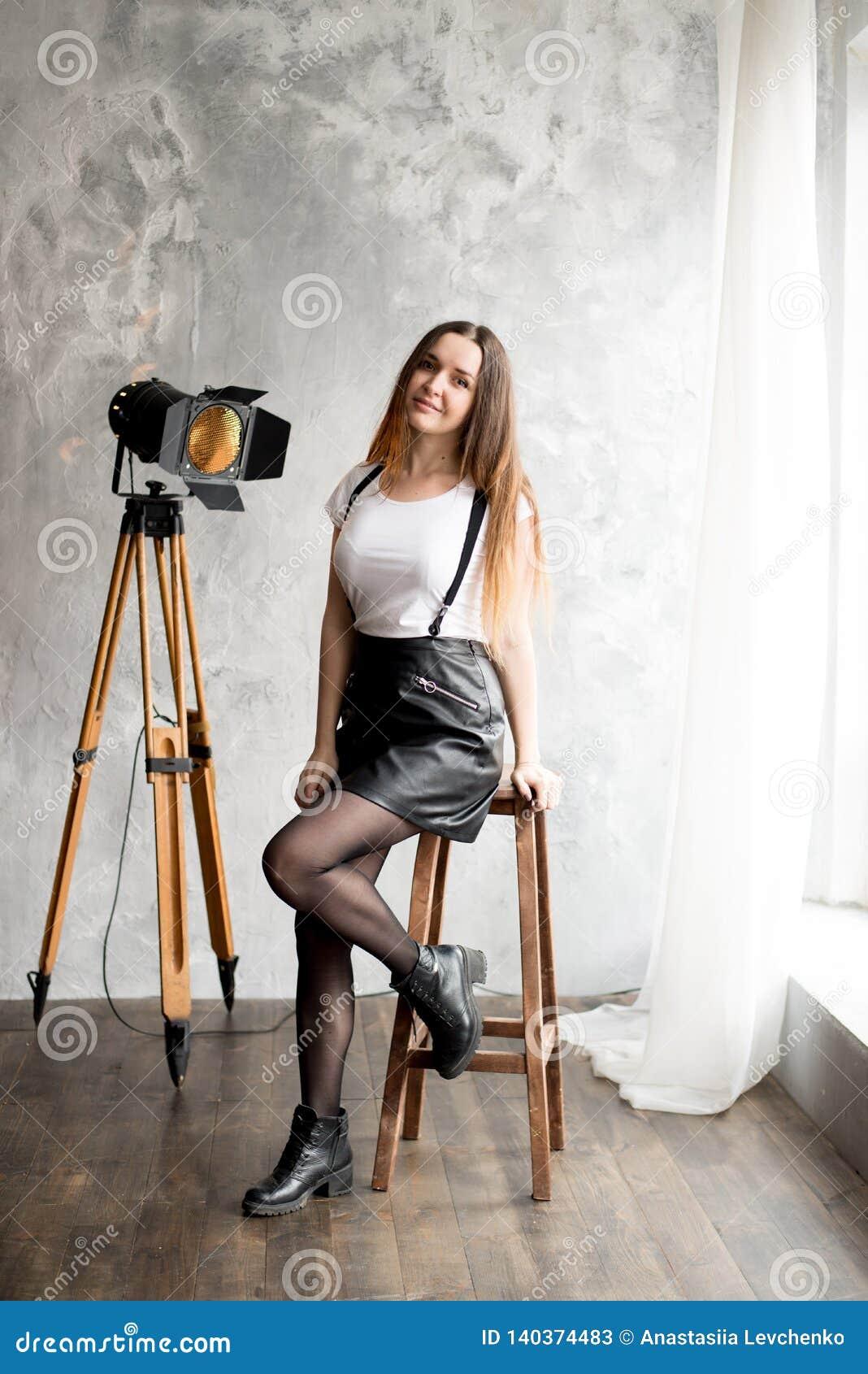 Pełny długość portret uśmiechnięty młodej kobiety obsiadanie na krześle