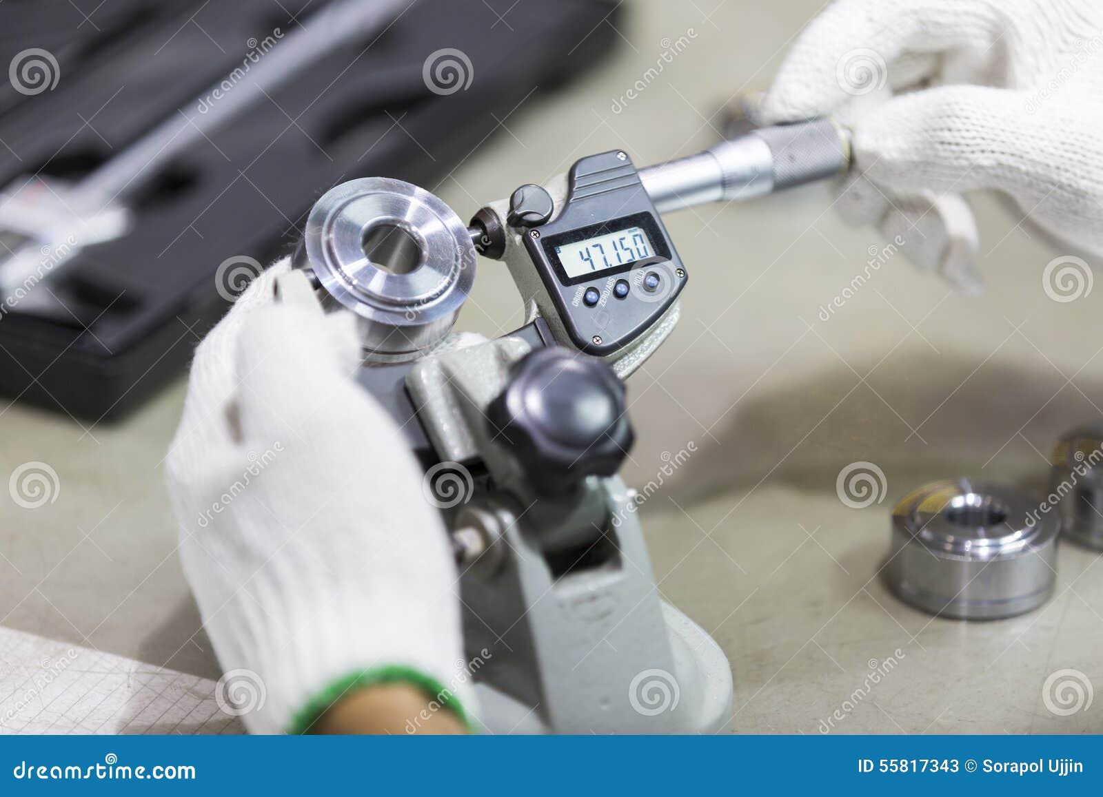 Peça automotivo da inspeção do operador pelo micrômetro