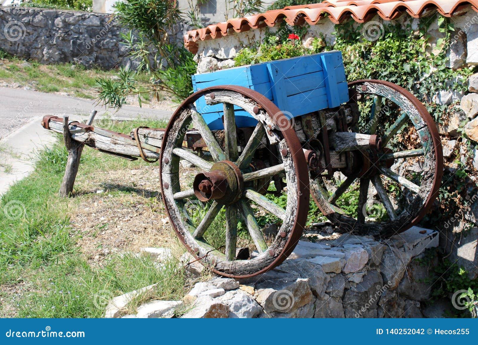 Peça dilapidada retro do vintage do transporte de madeira do cavalo com os quadros da roda do metal usados como a decoração do ja