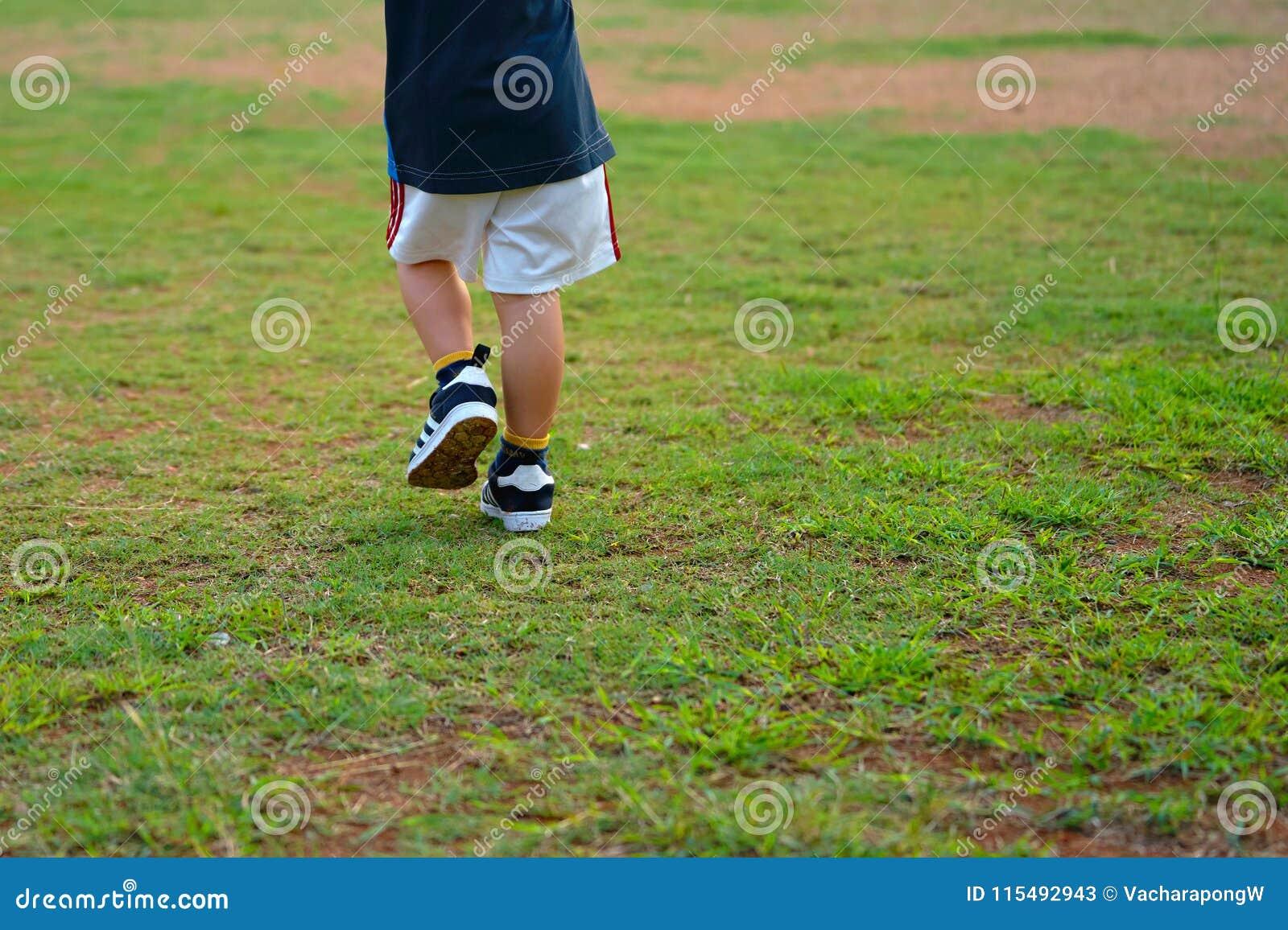 Peça do pé ou de corpo inferior do passeio ou da corrida da criança no campo de grama ou no l