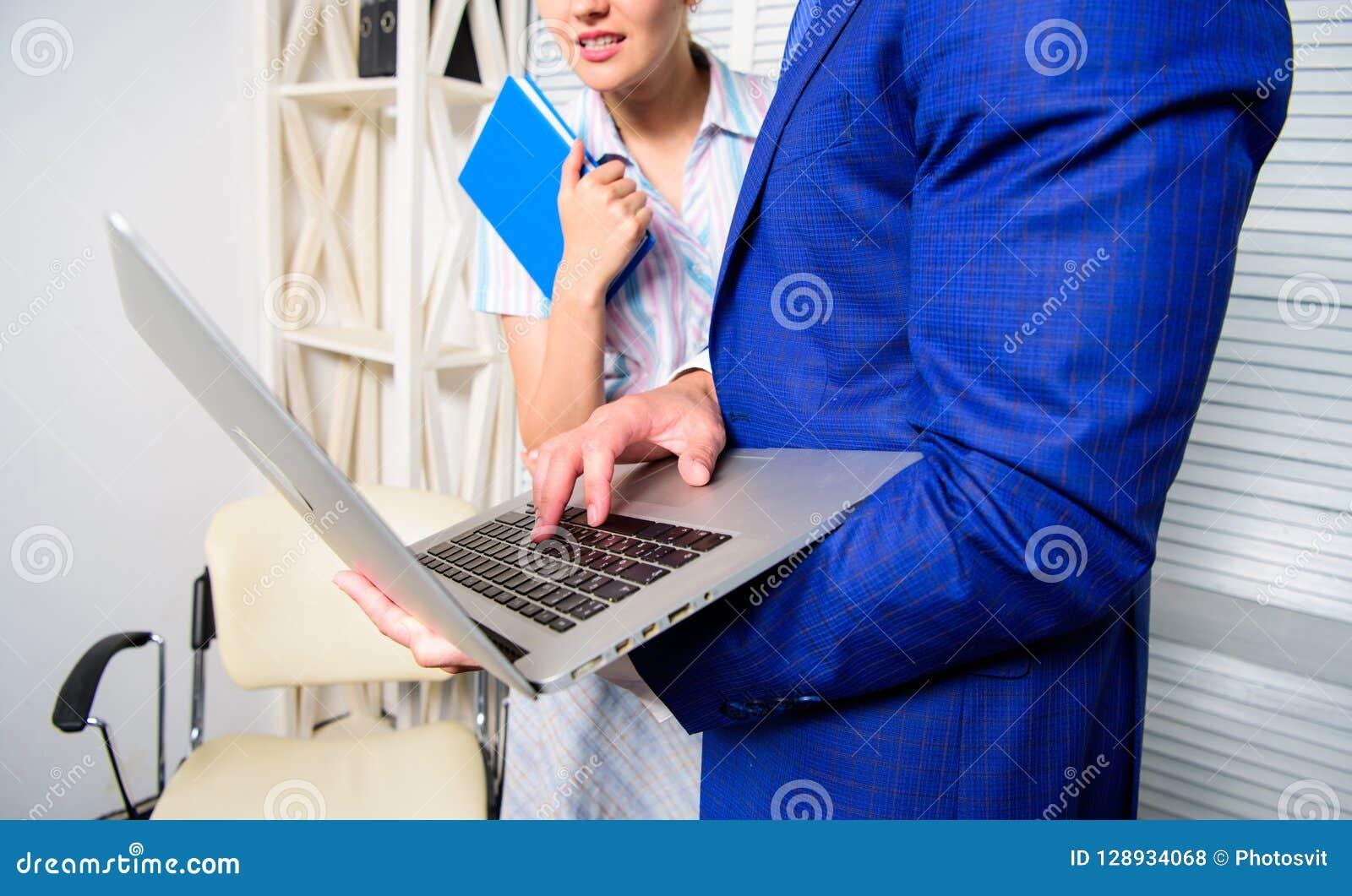 Peça a opinião do colega Internet surfando do portátil da posse do homem de negócios com colega Mostra do sócio comercial do escr