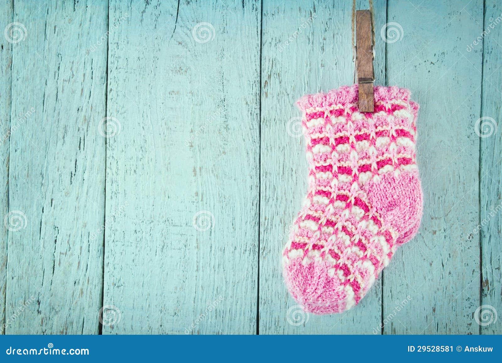 Peúgas cor-de-rosa do bebê em um fundo de madeira azul