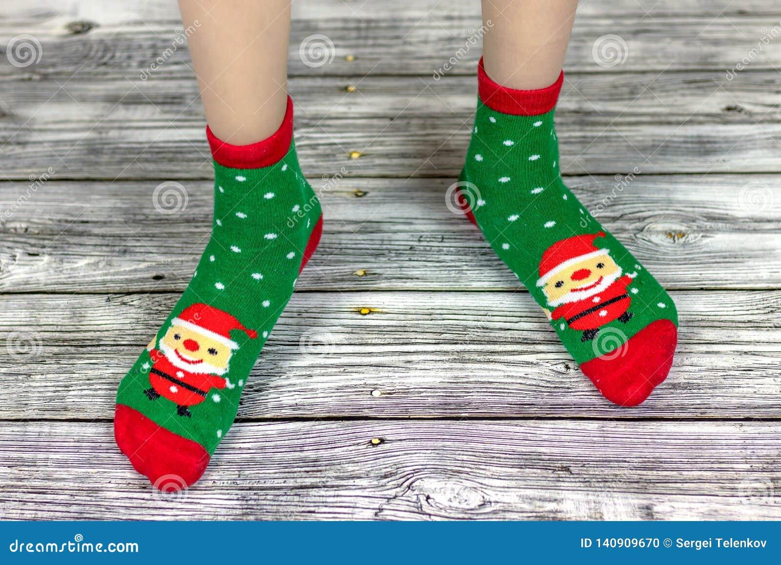 Peúgas do bebê do Natal, feriado feliz Ano novo e Feliz Natal Pés do bebê em peúgas vermelhas e verdes com