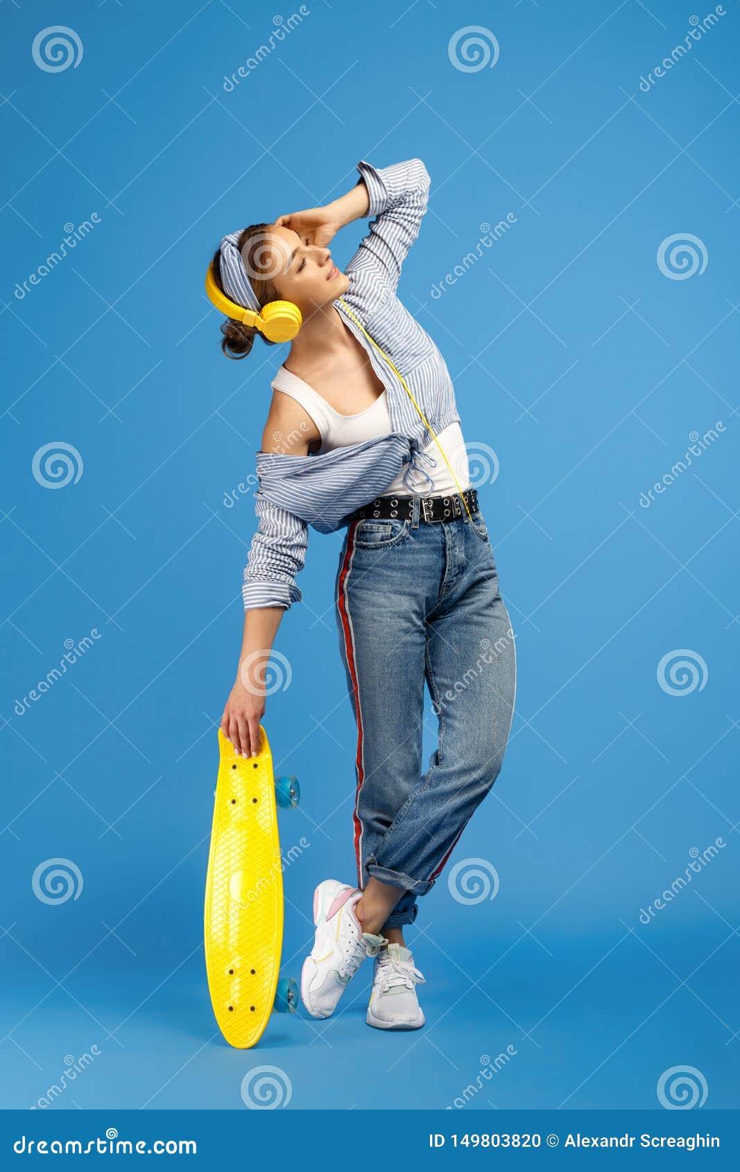 Pełna długości fotografia dosyć beztroska młoda kobieta słucha muzykę z żółtymi hełmofonami z centem lub deskorolka