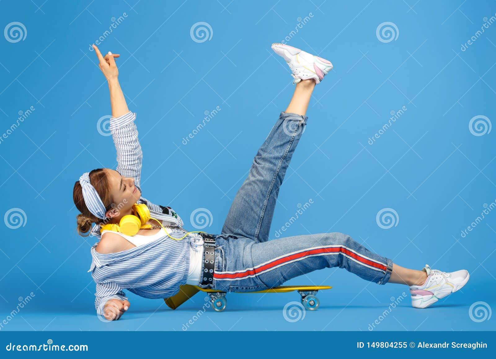 Pełna długości fotografia szczęśliwa beztroska młoda kobieta siedzi na cencie lub deskorolka nad błękitem z żółtymi hełmofonami