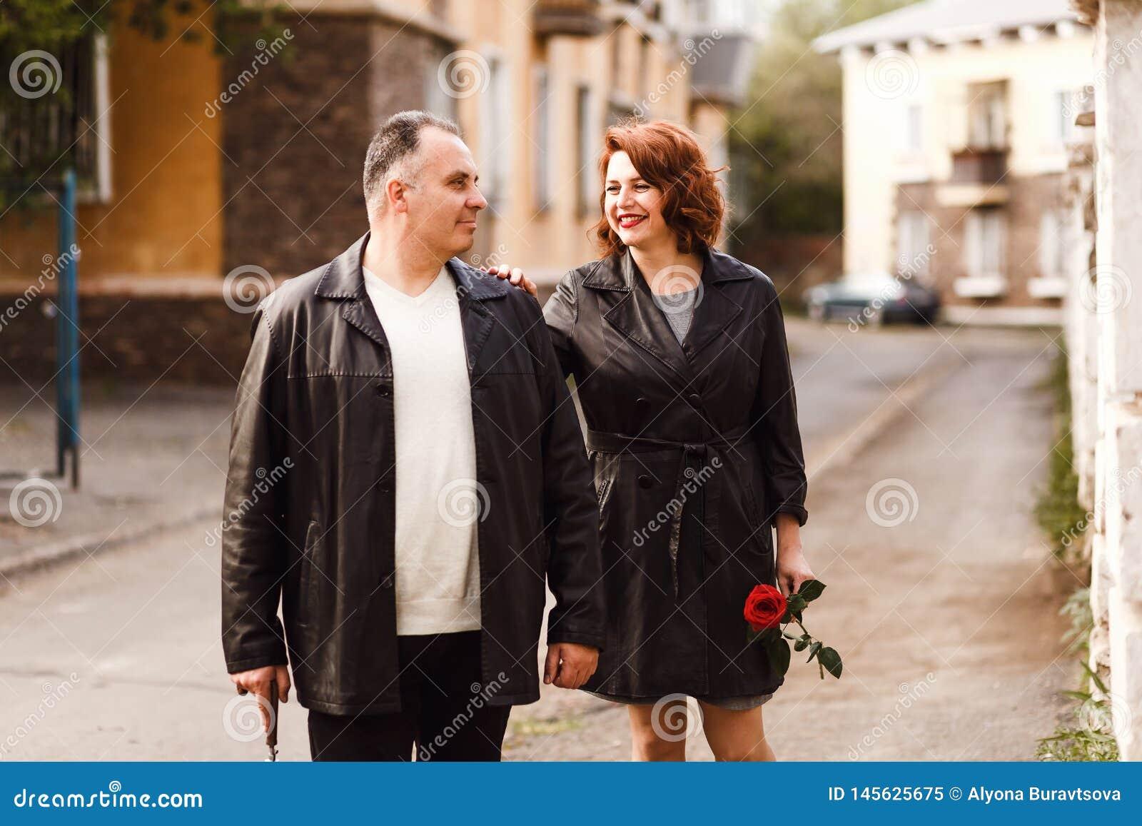 Pełnoletnia para w skórze pokrywa odprowadzenie przez miasto ulic w lecie Szczęśliwy mężczyzny i kobiety czterdzieści pięć lat