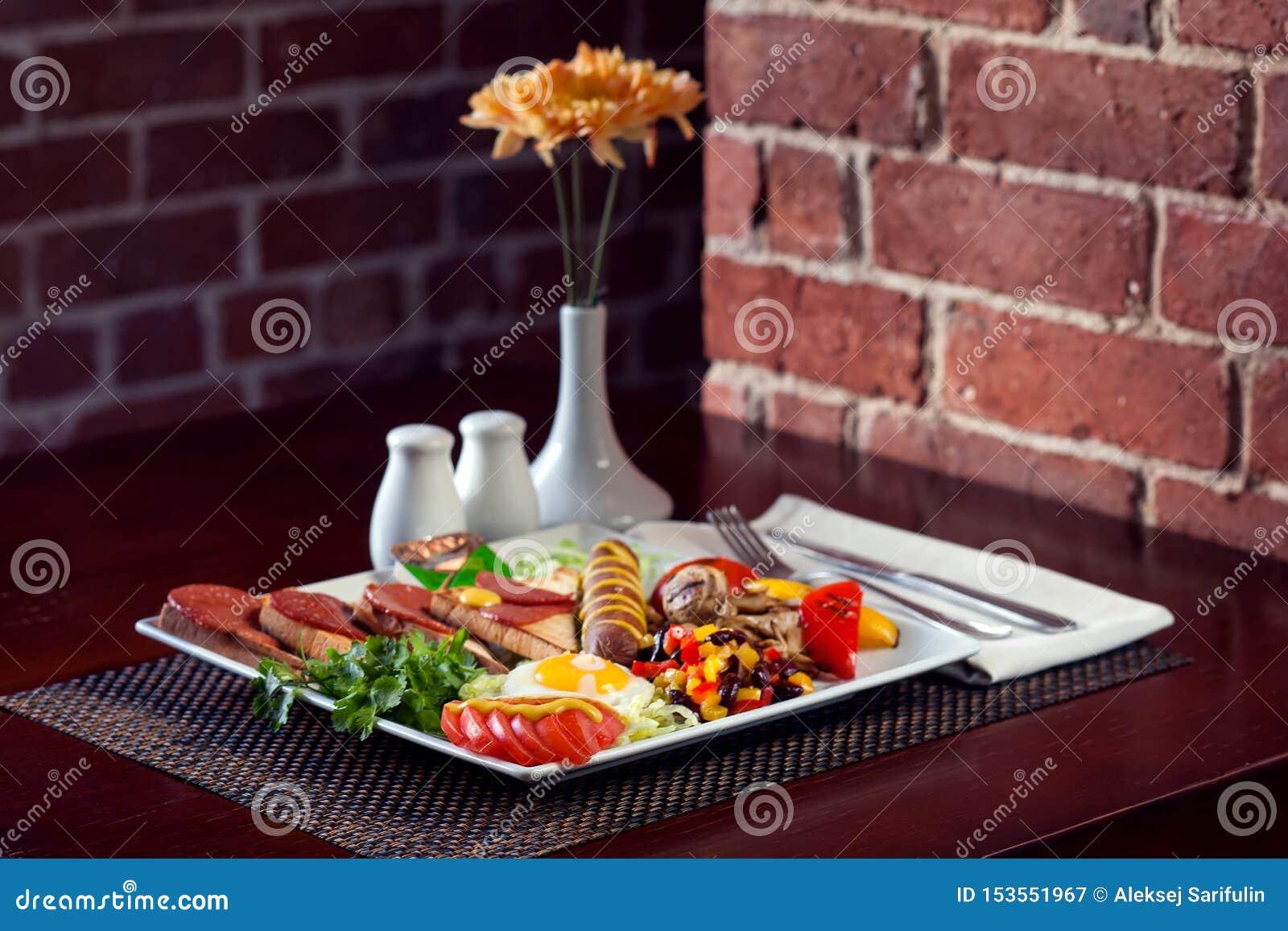 Pełny Angielski śniadanie wliczając kiełbas, piec na grillu pomidorów i pieczarek, jajko, bekon, piec fasole i chleb Jedzenie i r