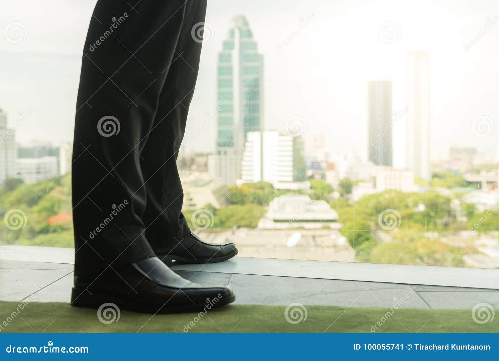 Pełny długość plecy widok pomyślny biznesmen w kostium pozyci w biurze z rękami na jego talii