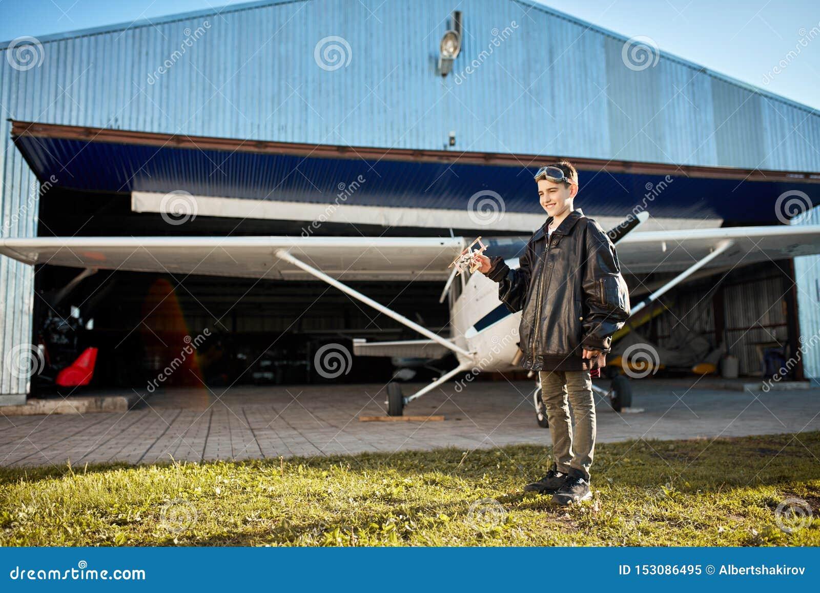 Pełny długość widok uroczy dzieciak, bawić się outside samolotu hangar z zabawka samolotem