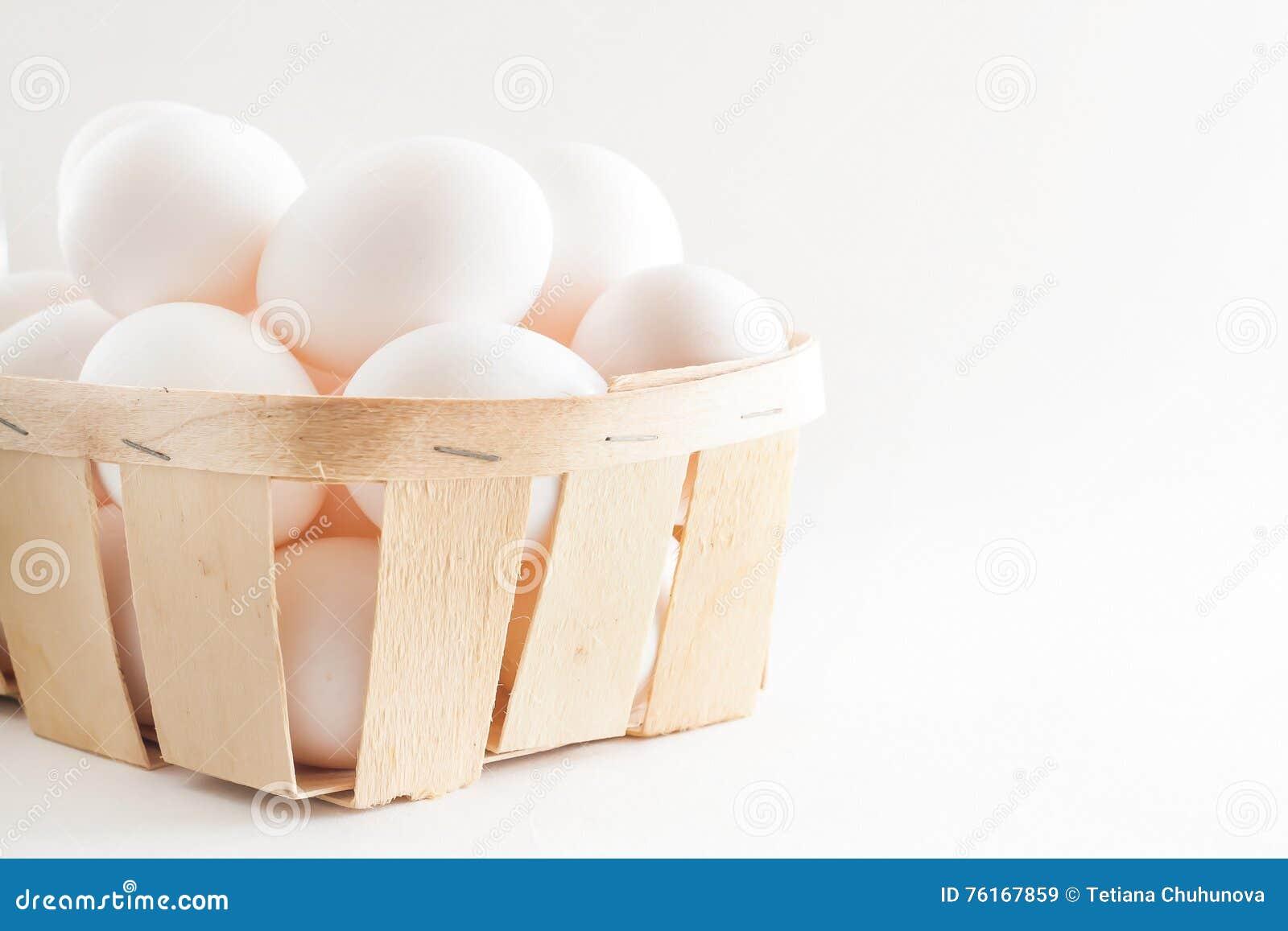 Pełny kosz świezi jajka na białym tle