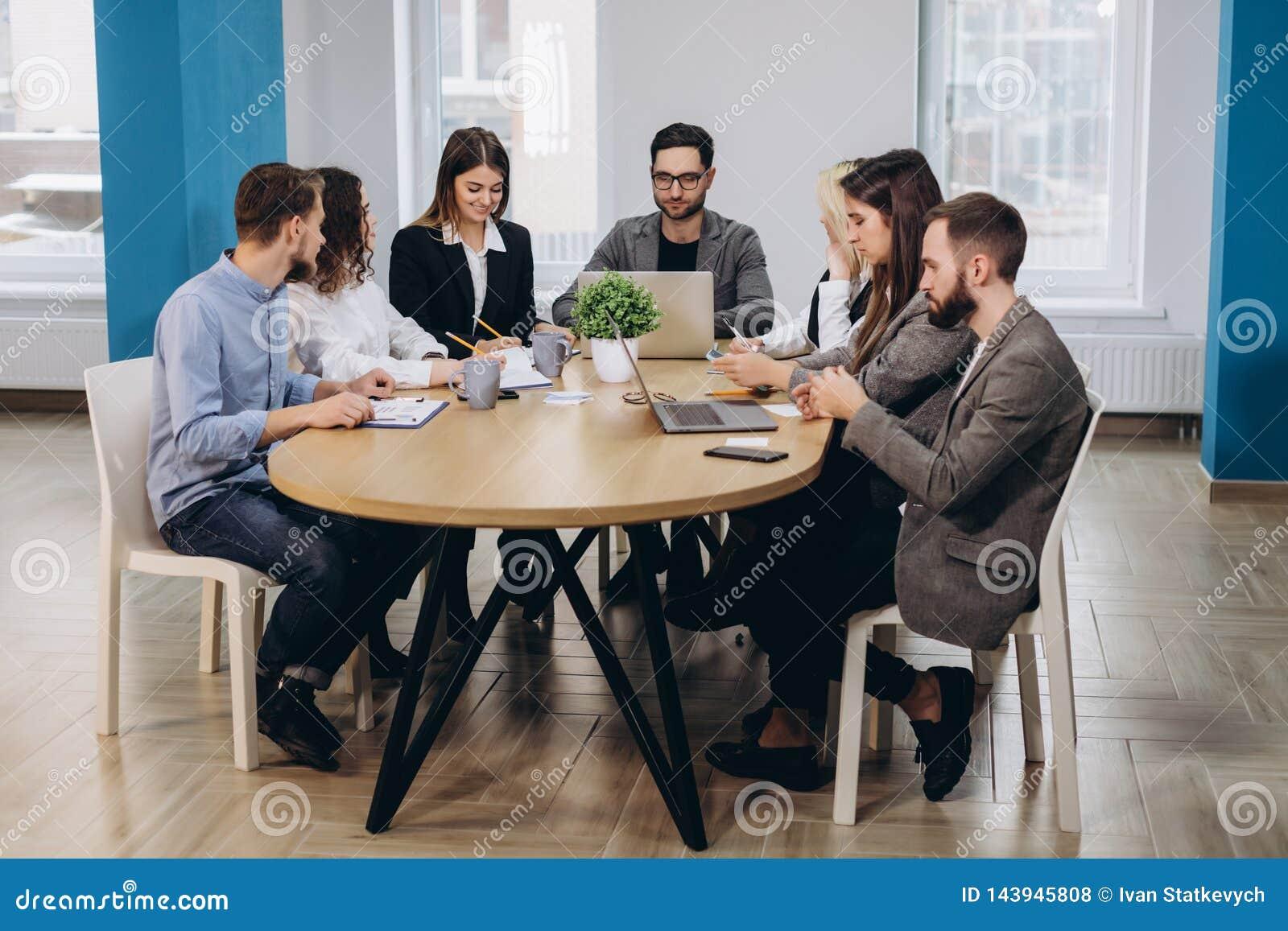 Pe?na koncentracja przy prac? Korporacyjni dru?ynowi pracuj?cy koledzy pracuje w nowo?ytnym biurze