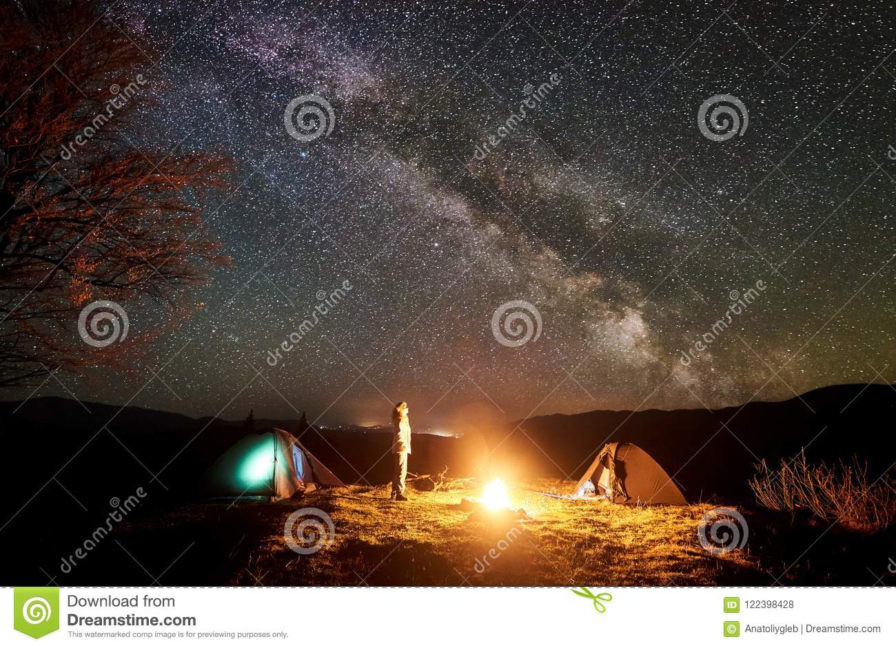 Night camping in mountains. Female hiker resting near campfire, tourist tent under starry sky