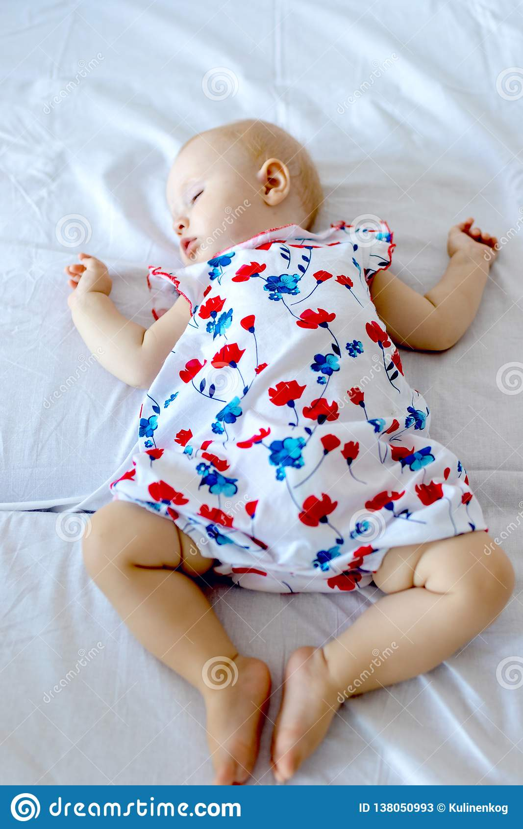Peaceful newborn baby lying on a bed