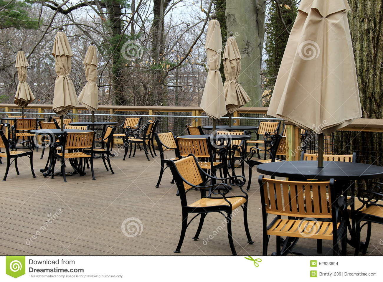 Peaceful Scene Of Tables And Chairs With Tied Umbrellas On Outdoor