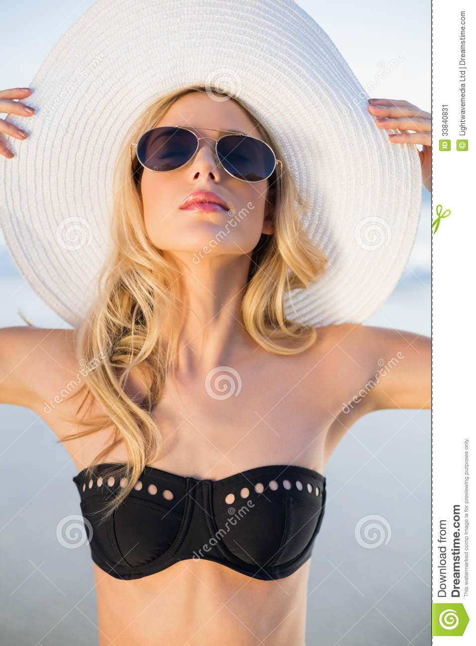 peaceful sensual blonde in elegant black bikini posing