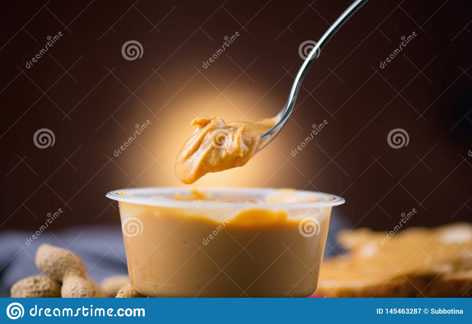 Peanut butter. Creamy smooth peanut butter in a jar on a table. Spoon of Natural nutrition. Organic food