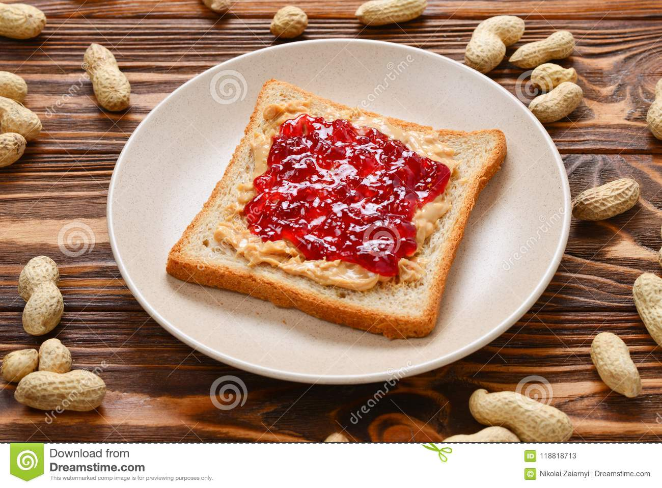 Peanut butter and jelly sandwich on wooden background.