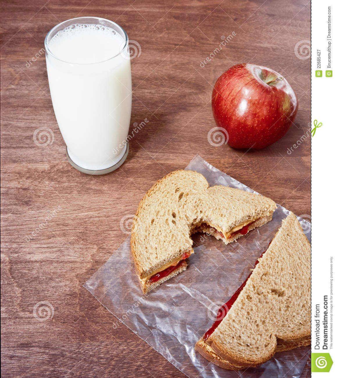 Peanut Butter sandwich with a glass of milk and an apple. Bite taken ...