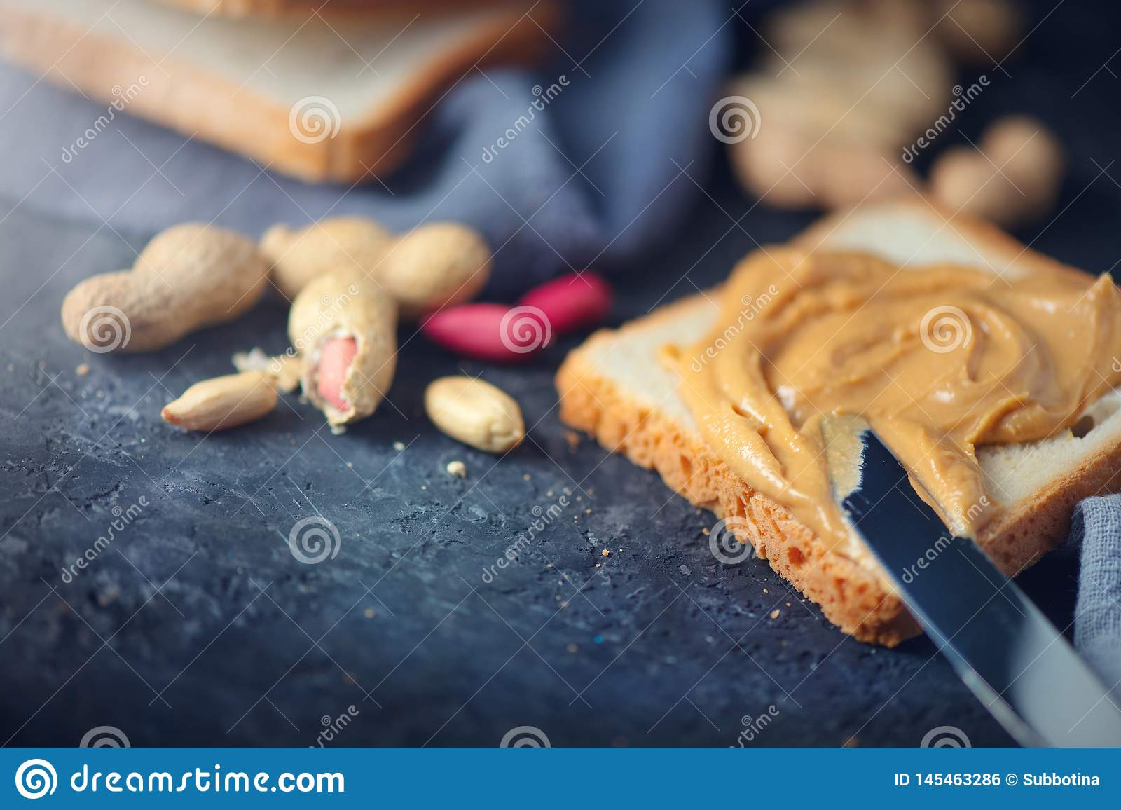 Peanut butter. Person making peanut butter sandwiches, healthy food. Woman smears butter with a knife