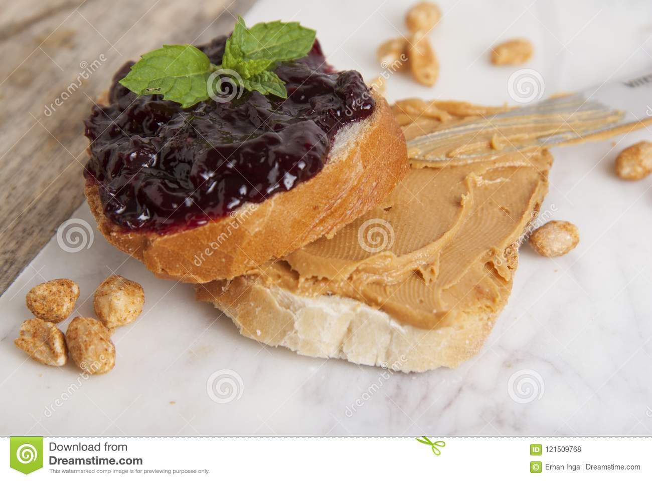 Peanut butter and raspberry jelly sandwich on white background. Sweet breakfast or snack. Close up.