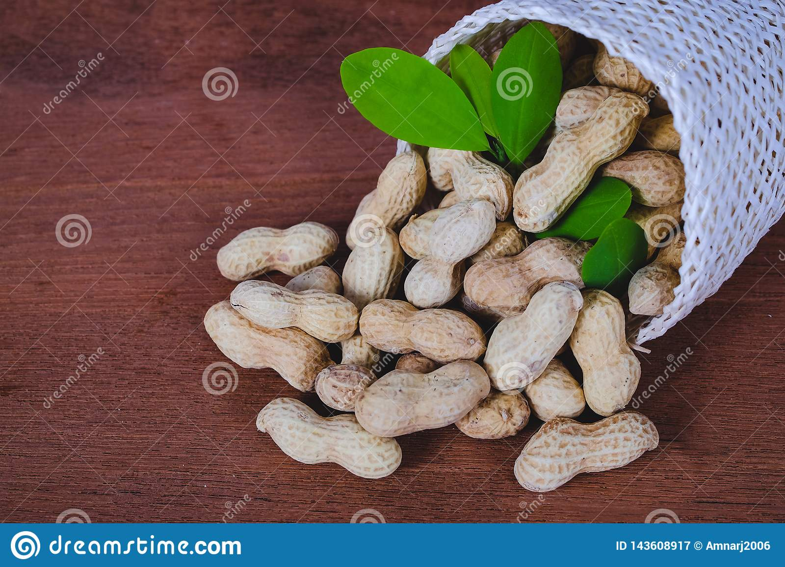 Peanut spill out of basket on wood