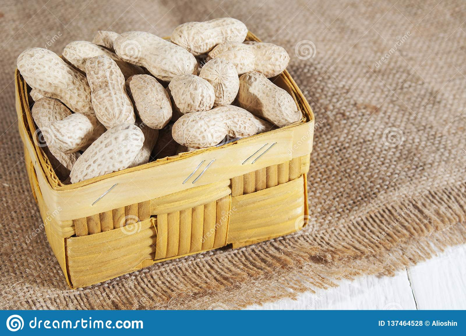 Groundnuts In Basket On A Burlap On A White Wooden Table