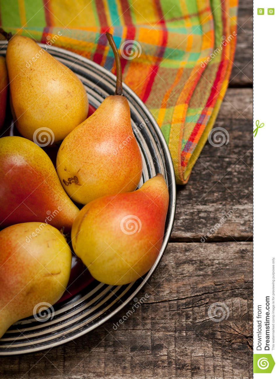 Pears on the dish and cloth on the old wood backing