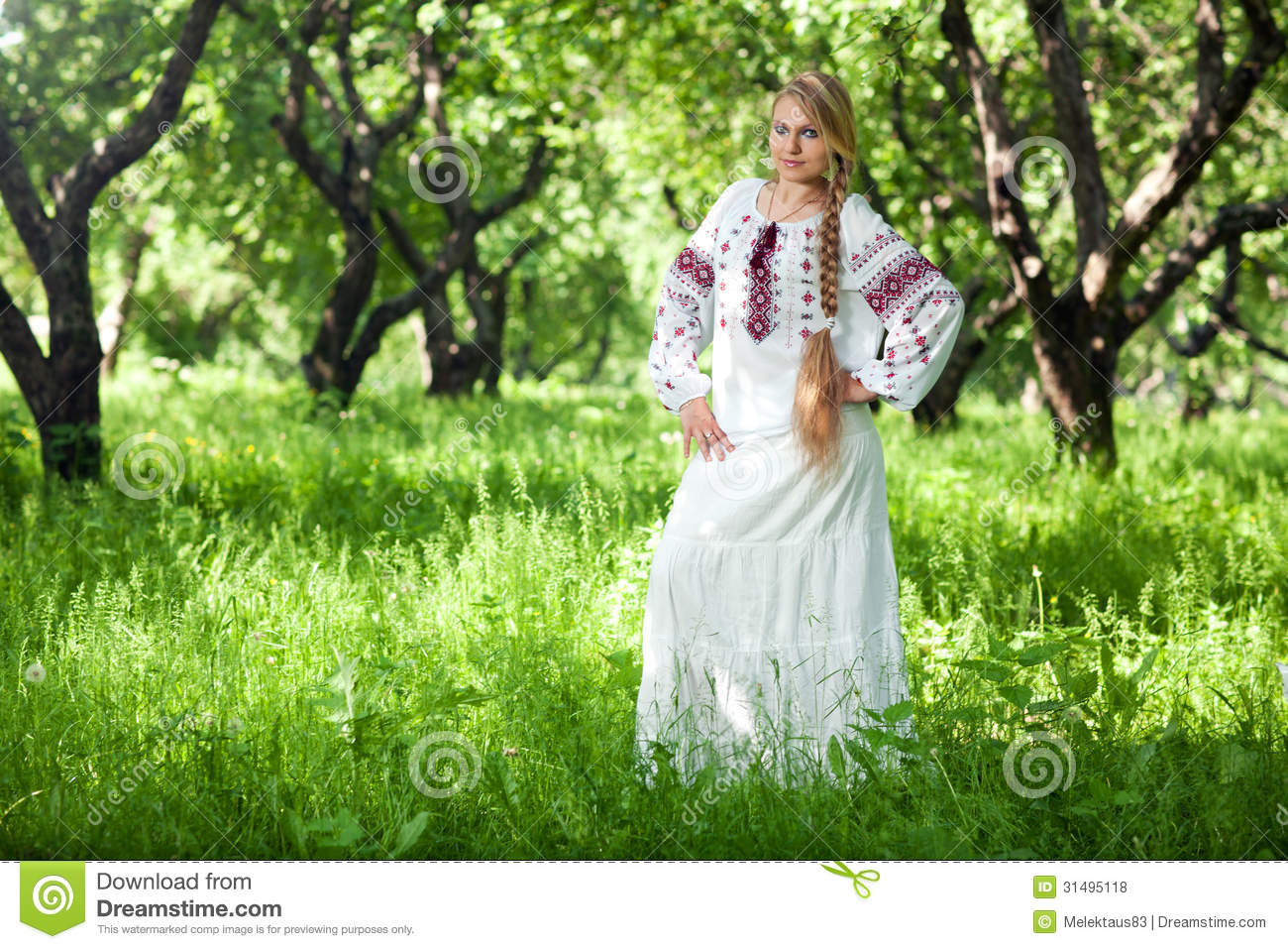 Beautiful young peasant girl with a long braid is in the summer garden