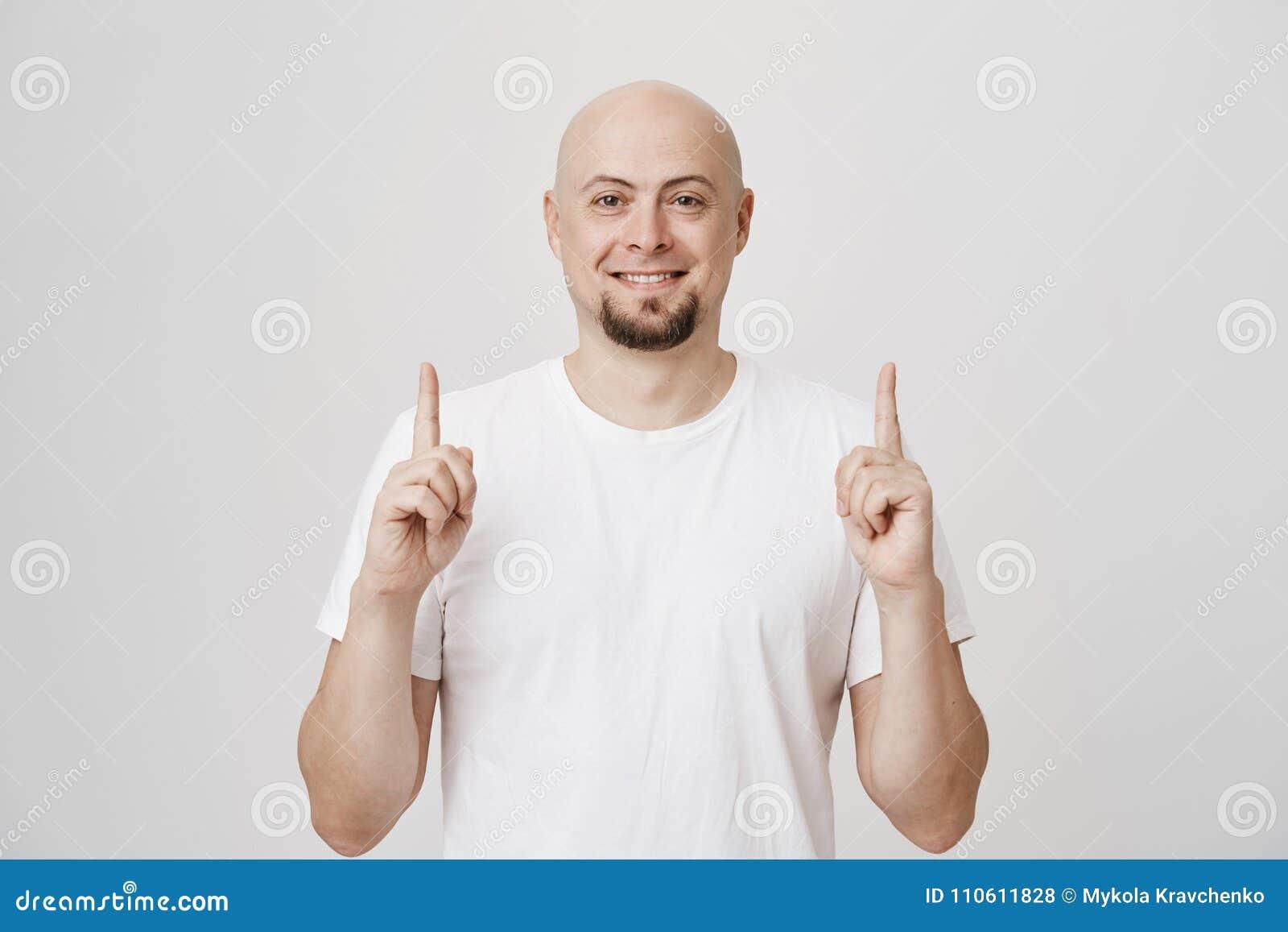 Peased knap Kaukasisch gebaard mannetje die ruim terwijl het wijzen omhoog op met beide wijsvingers glimlachen, die bevinden zich
