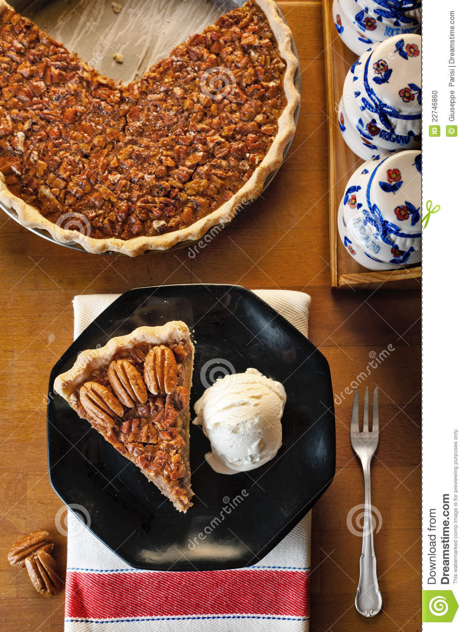 pecan pie served with vanilla ice cream on a black dish, the whole pie ...
