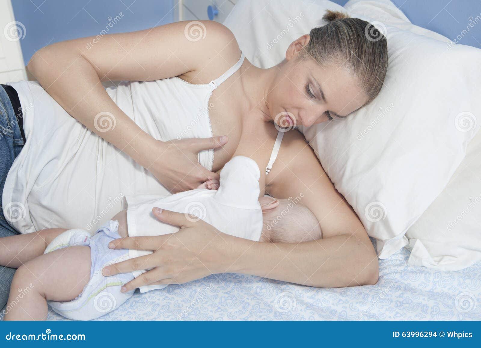 Pecho de alimentación de la madre joven su bebé que pone en su dormitorio