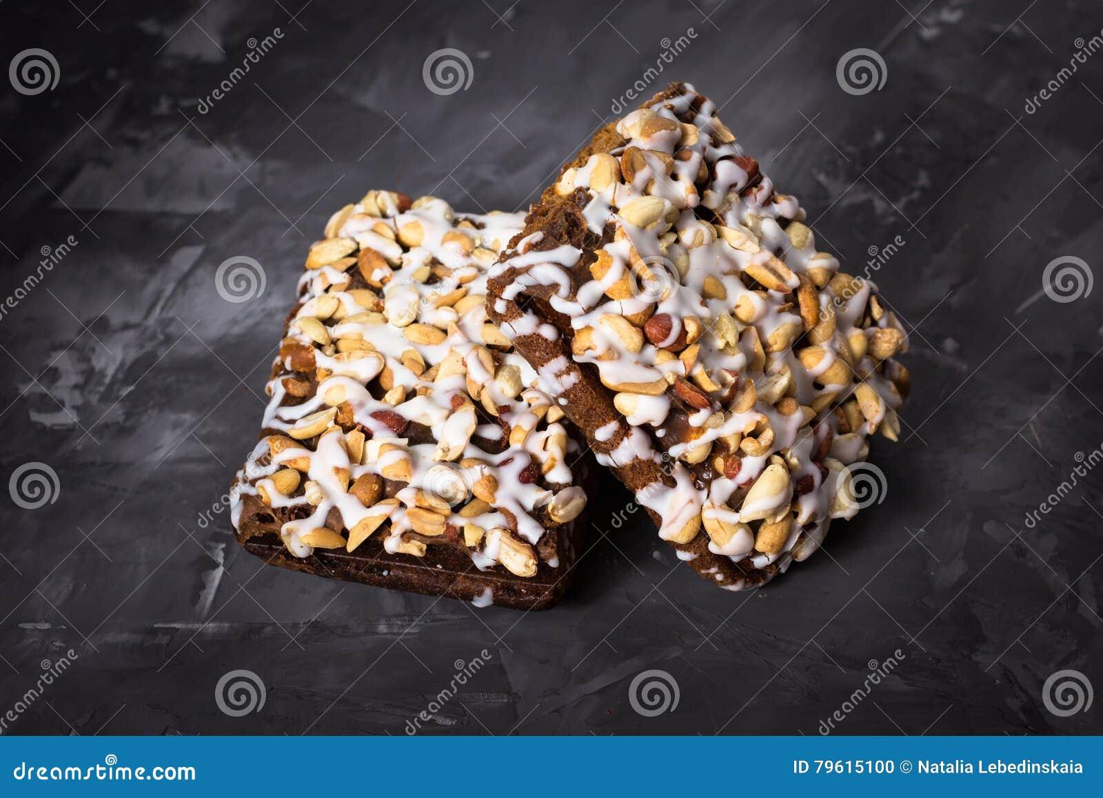 Pedaço de bolo, cookies com crosta de gelo nuts e branca no CCB concreto