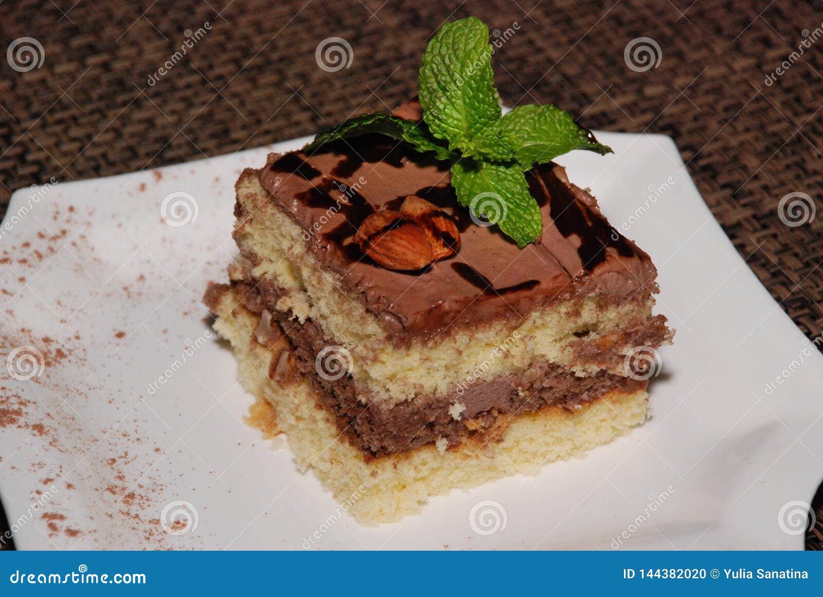Pedaço de bolo quadrado com chocolate e amêndoa na placa branca