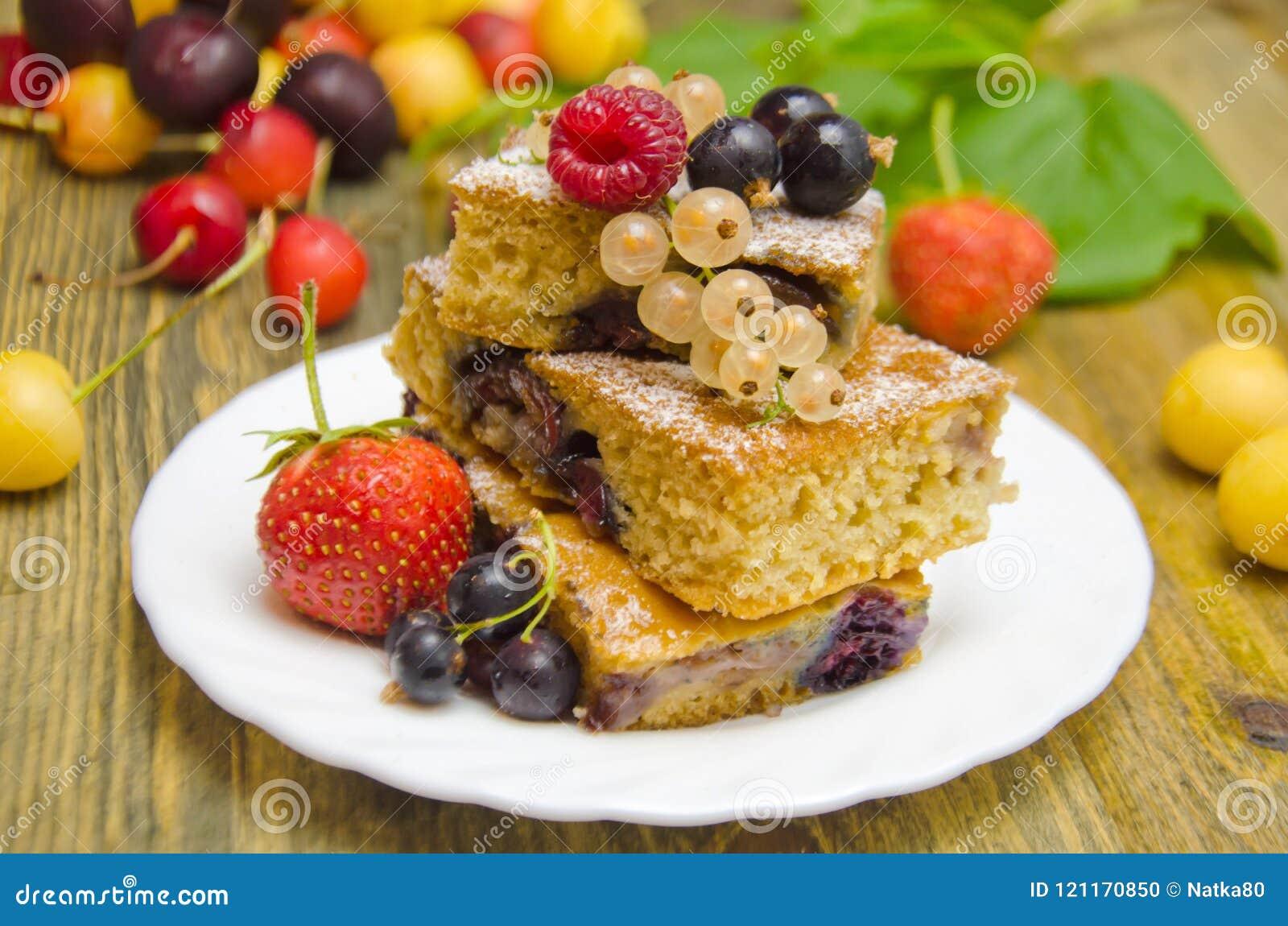 Pedaços de bolo com bagas e as bagas frescas do corinto e da cereja da morango no fundo de madeira