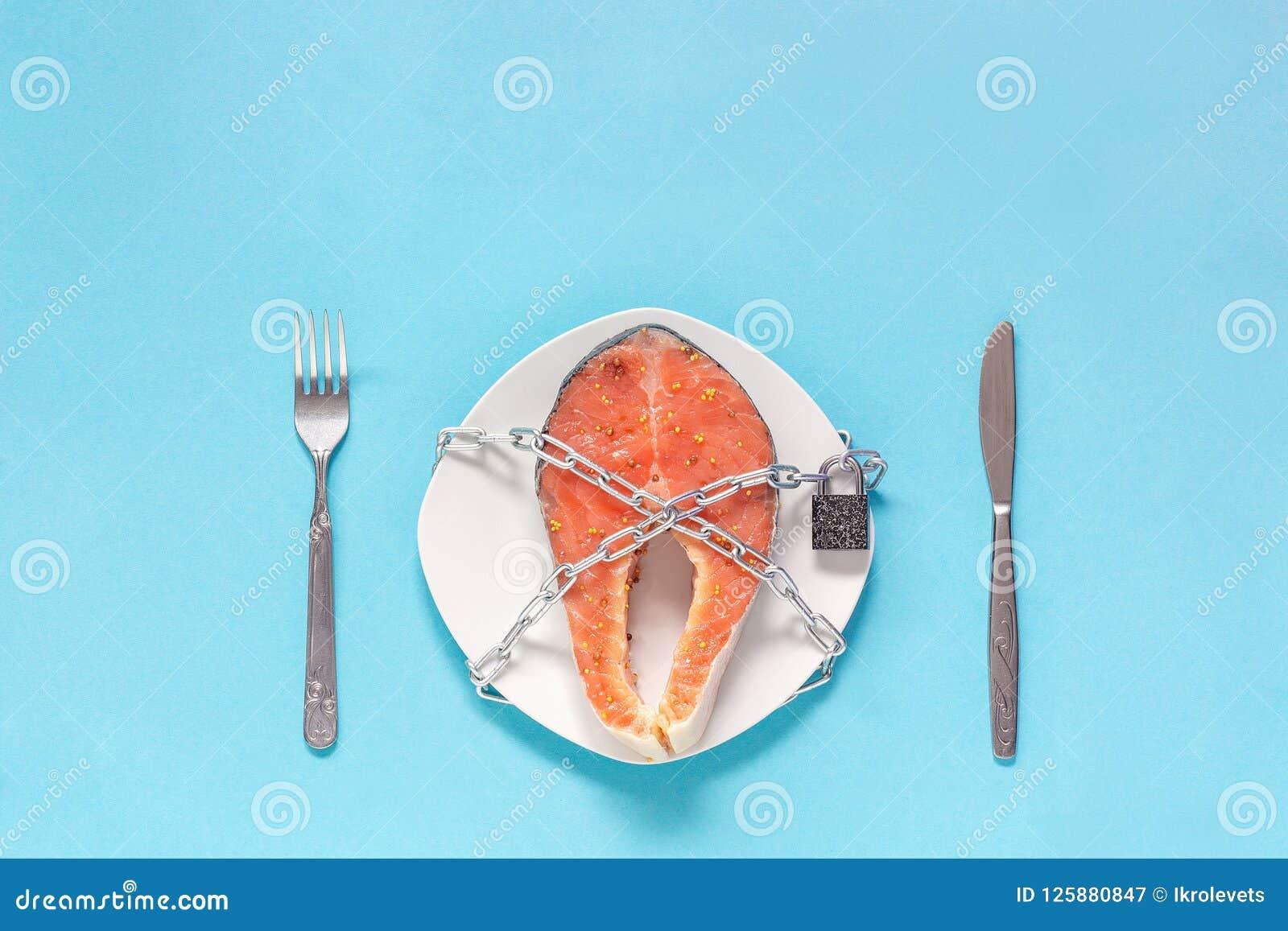 Pedazo de pescados rojos en la placa y cadena con el candado cerrado