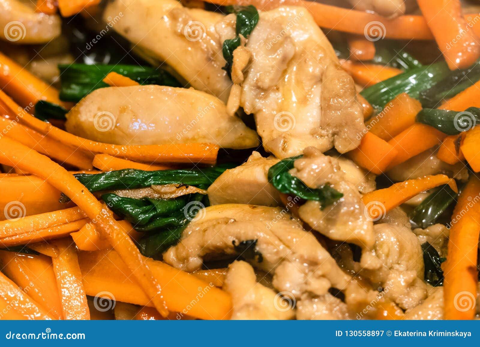 Pedazos de carne del pollo que fríen con las zanahorias cortadas