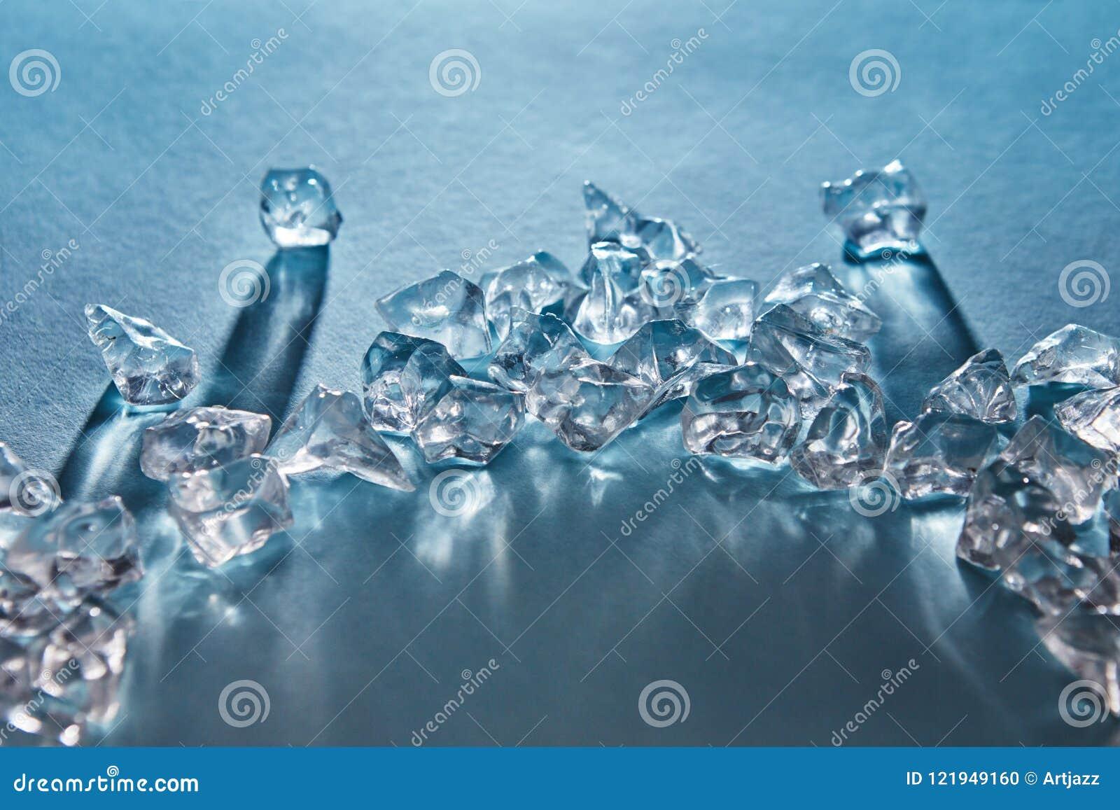 Pedazos de cubos de hielo machacados en bajo la forma de arco con las sombras largas y de reflexiones en la superficie en un azul