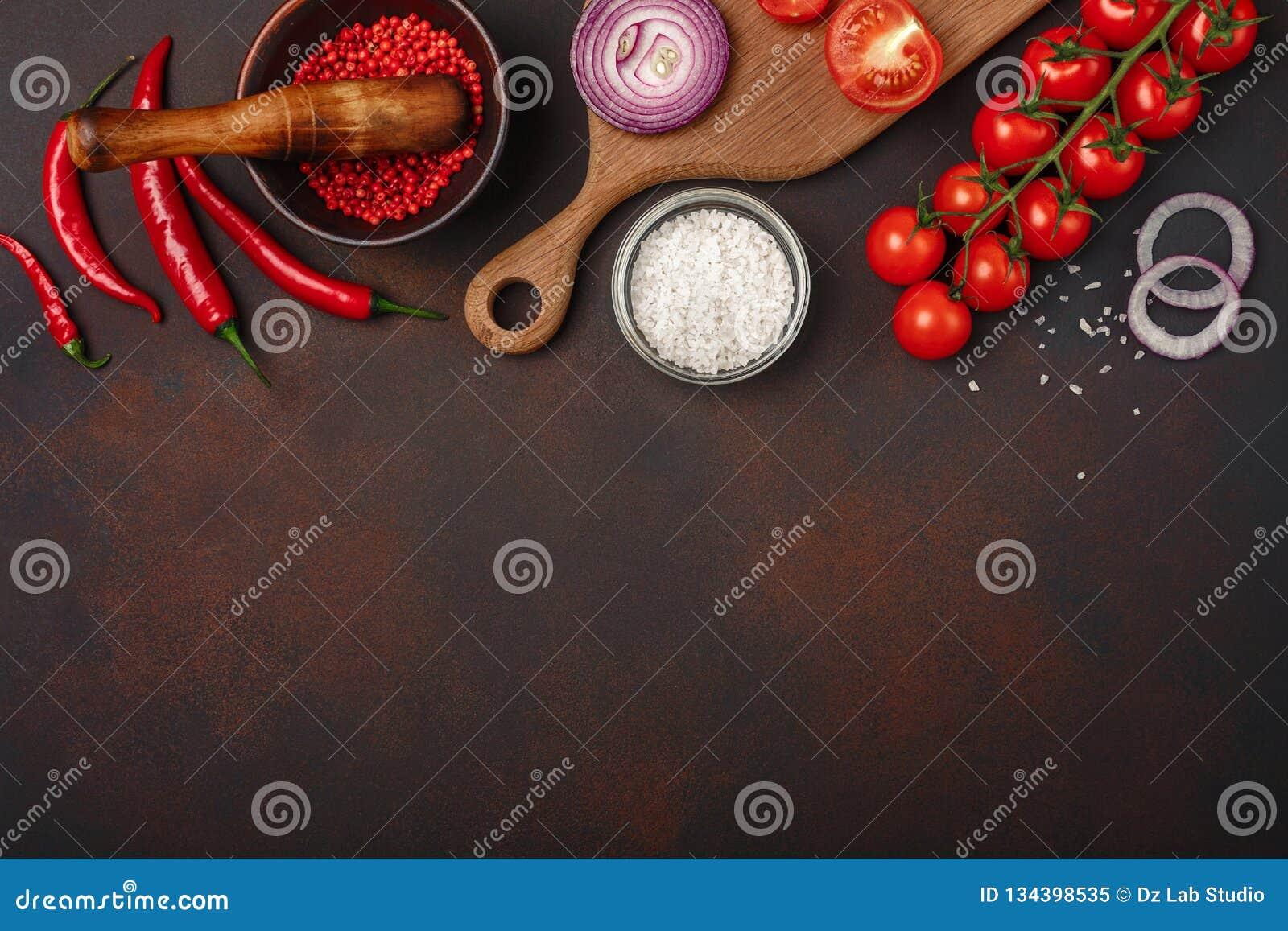 Pedazos de filete crudo del cerdo en tabla de cortar con los tomates de cereza, el romero, el ajo, la pimienta roja, la hoja de l