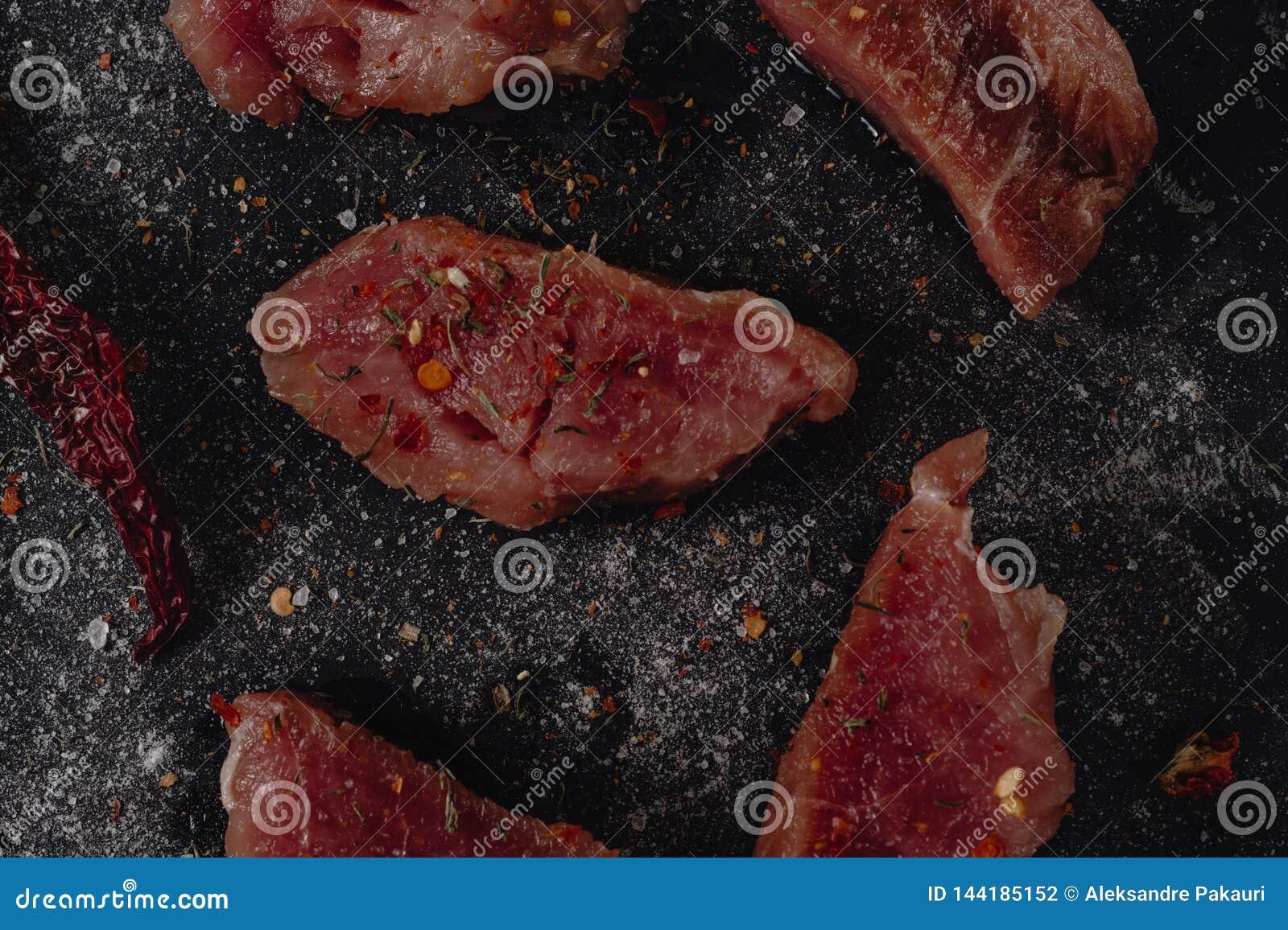 Pedazos de filete crudo de los medalions del cerdo con las especias, la sal y la pimienta en un fondo oscuro del bastón en el est