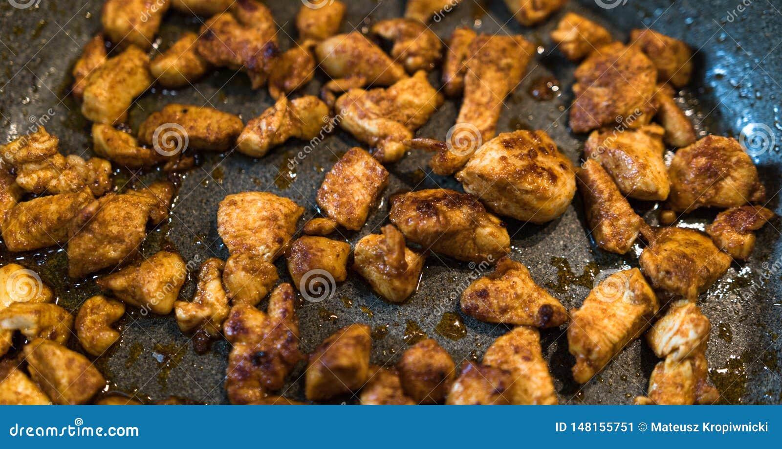 Pedazos de pollo sazonado fritos en una cacerola
