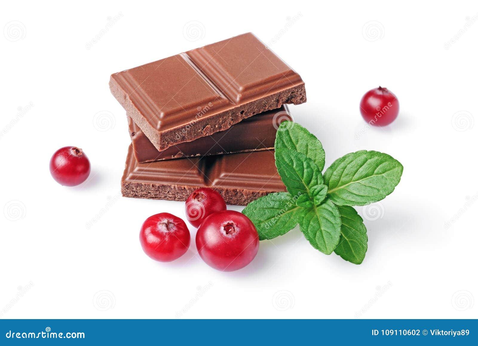 Pedazos del primer de barra del chocolate con leche con el arándano y la menta frescos