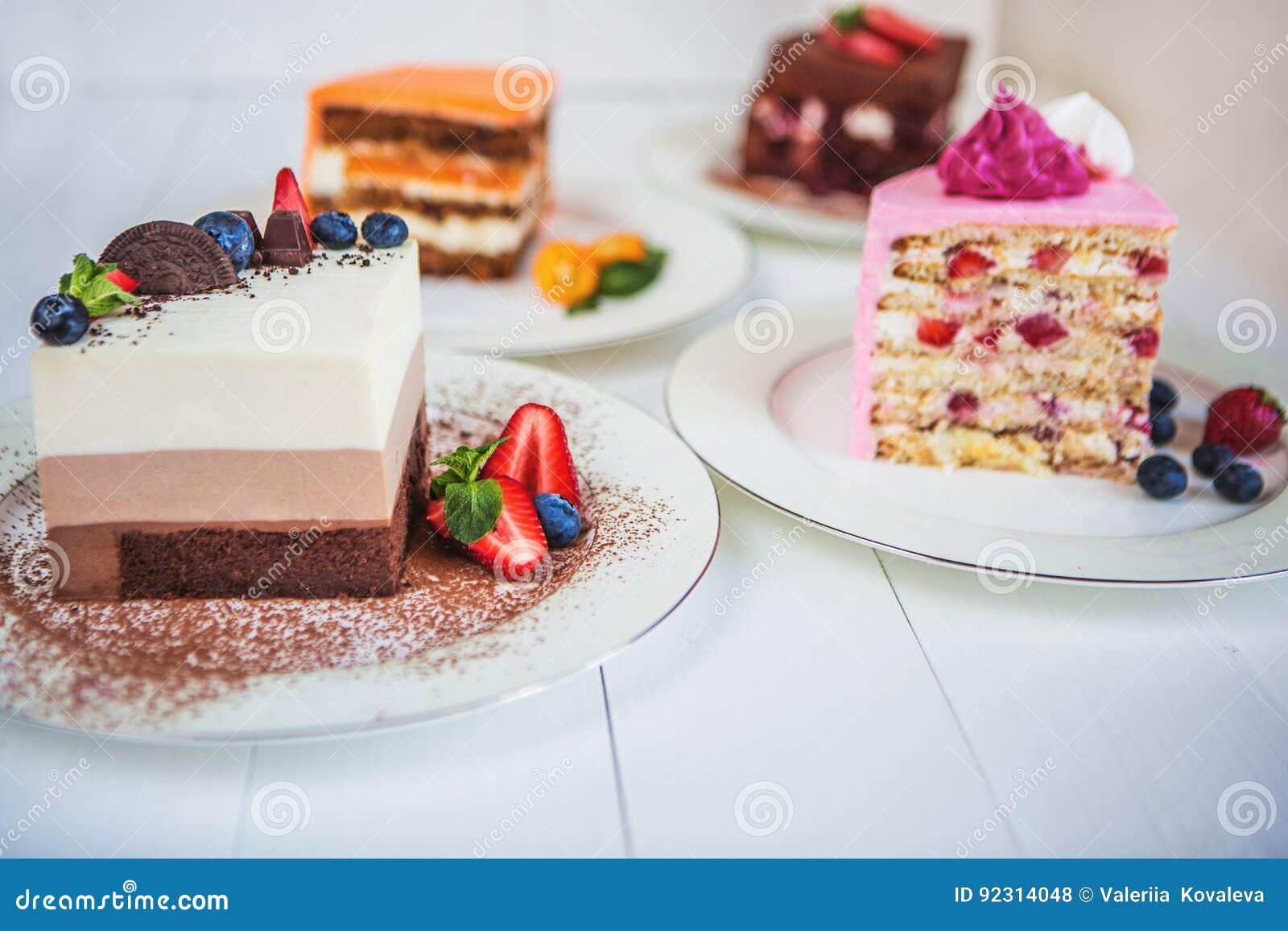 Pedazos grandes clasificados de diversas tortas: tres chocolate, zanahoria, fresa, chocolate Las tortas se adornan con las bayas