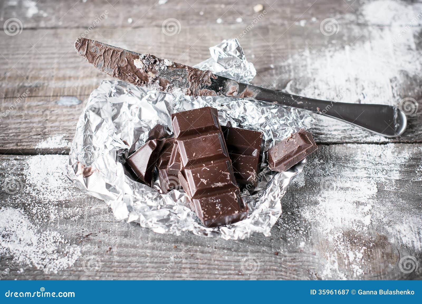 Pedazos oscuros negros del chocolate en fondo de madera.
